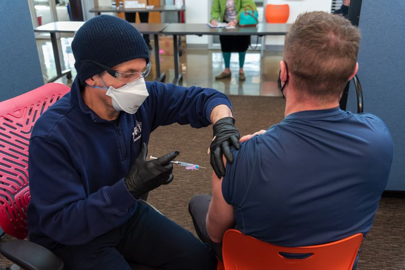 FILE PHOTO - Tualatin Valley Fire and Rescue employees help administer vaccinations at Clackamas Community College's Wilsonville campus in early March.