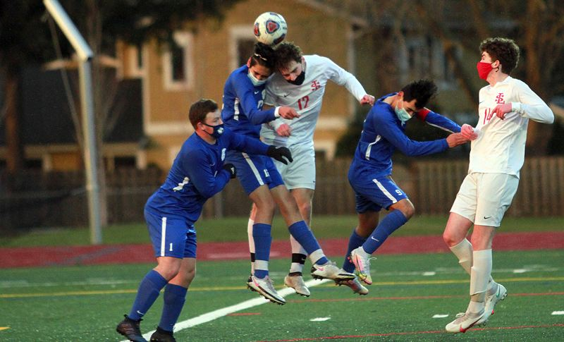 PMG PHOTO: MILES VANCE - La Salle's Kainoa Taylor (no. 12 in white) goes up for a header against Hillsboro's Carlos Geovanni Aguilar during the Falcons' 5-0 Northwest Oregon Conference win at Hillsboro High School on Thursday, March 25.