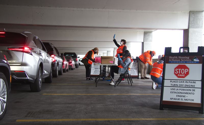 PMG PHOTO: SAM STITES - Volunteers with Clackamas Fire District No. 1, the Community Emergency Response Team and University of Portland's nursing program prepare shots to be adminstered in a drive-thru clinic set up inside a parking garage at the Clackamas Town Center.