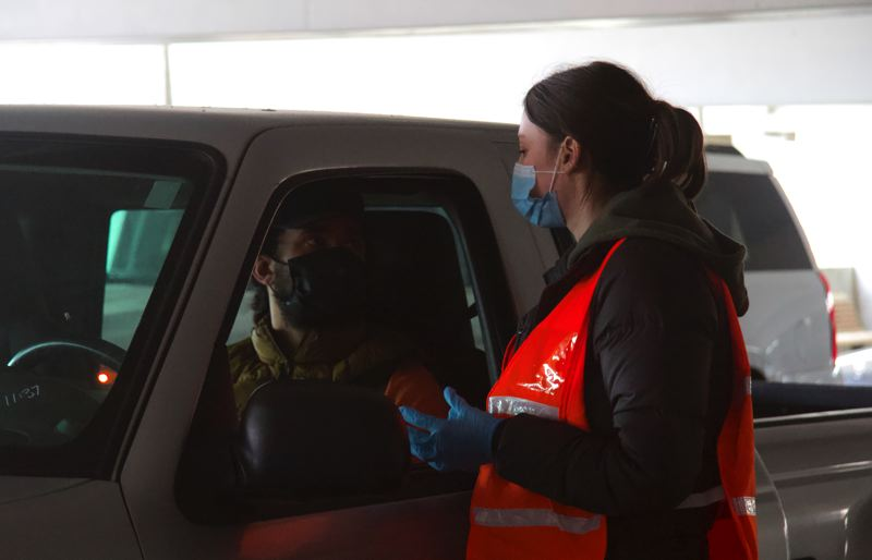 PMG PHOTO: SAM STITES - A volunteer gives information to a Clackamas County resident who just received the COVID-19 vaccine while they wait 15 minutes after their shot to exit the parking garage.