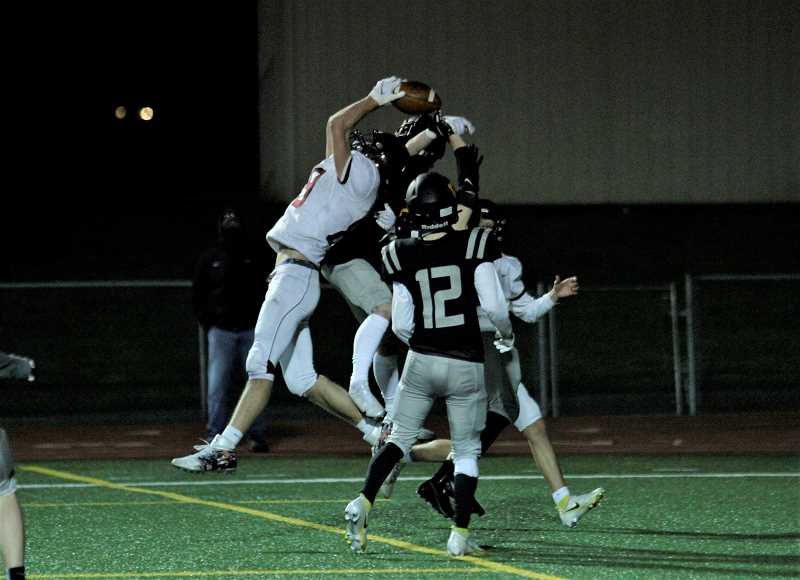 PMG PHOTO: WADE EVANSON - Forest Grove's Jake Steltenpohl leaps for a late touchdown catch against St. Helens Friday night, March 26, at St. Helens High School.