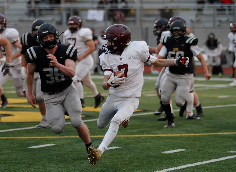PMG PHOTO: WADE EVANSON - Forest Grove's Kyle Ulloa carries the ball during the Vikings' game against St. Helens Friday night, March 26, at St. Helens High School.