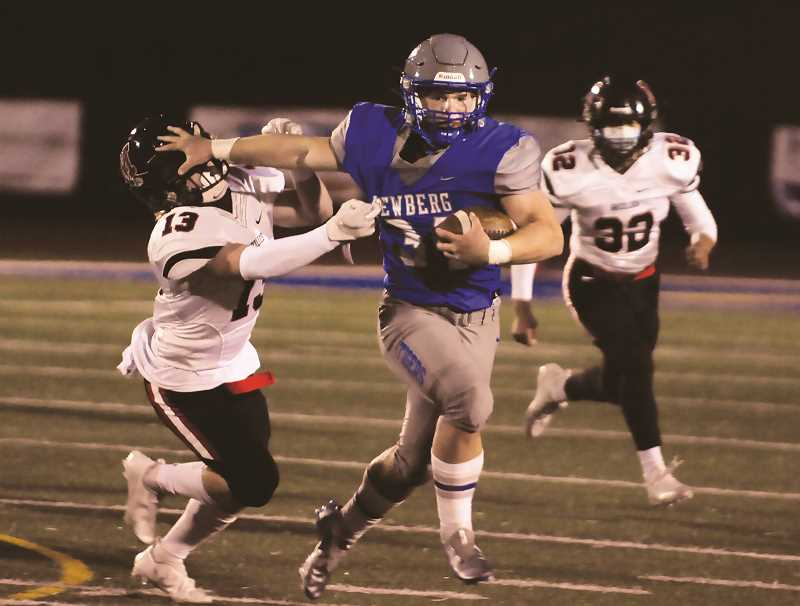 PMG PHOTO: GARY ALLEN - Newberg runningback Hudson Davis plows through the McMinnville defense in the Tigers' 56-9 thrashing of the Grizzlies at home March 26.
