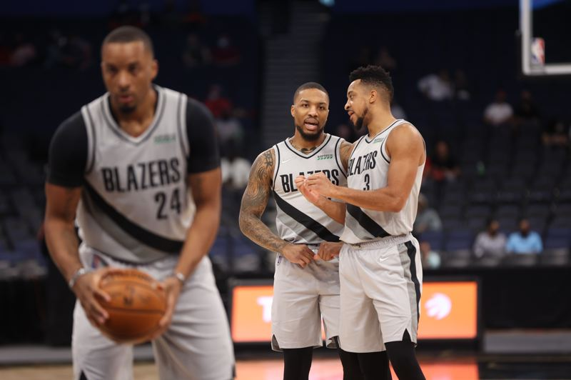 COURTESY PHOTO: BRUCE ELY/TRAIL BLAZERS - New player Norman Powell shoots free throws as new teammates Damian Lillard and CJ McCollum chat during Portland's win against Powell's old team, Toronto, on Sunday.