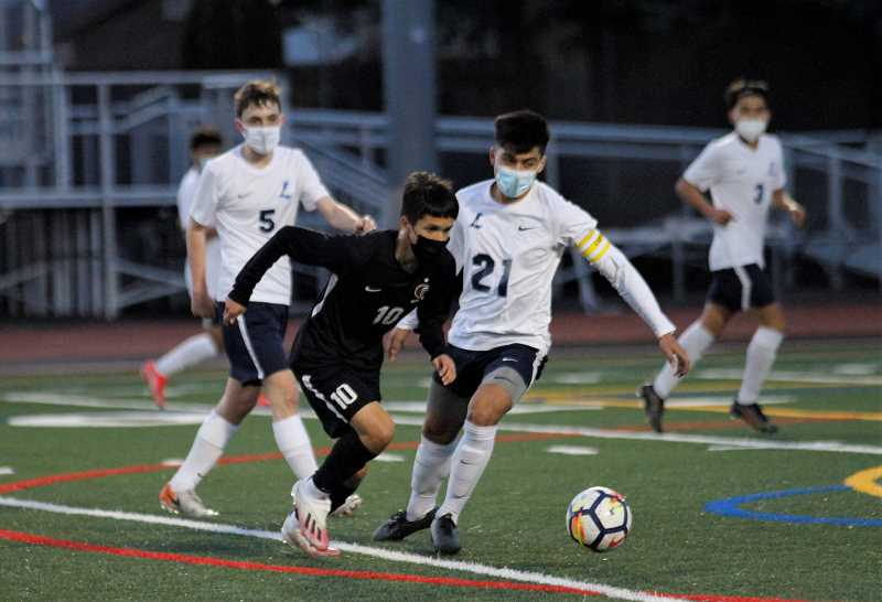 PMG PHOTO: WADE EVANSON - Glencoe's Miguel Lopez (10) and Liberty's Daniel Valencia (21) battle for a ball during the teams' conference game Wednesday, March 24, at Hare Field.