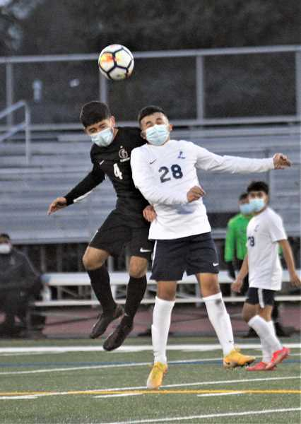 PMG PHOTO: WADE EVANSON - Glencoe's Ivan Alfaro (4) and Liberty's Brian Villasenor Guzman (28) rise up for a ball during the teams' conference game Wednesday, March 24, at Hare Field.