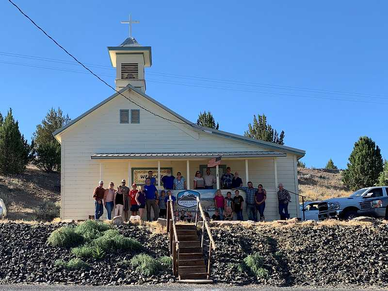 PHOTO SUBMITTED BY RORY RODGERS - Members of the Calvary Chapel congregation gather for a photo in front of the church on a sunny spring Sunday. The building, which is nearly 100 years old, was moved from Rager Ranger Station in the 1960s. It was originally a schoolhouse.