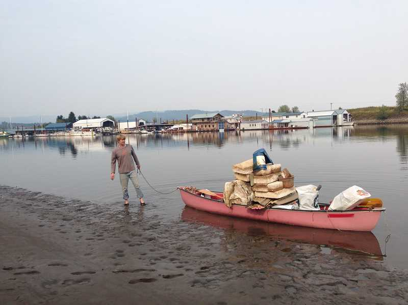 COURTESY PHOTO: HANNS HAEFKER - Hanns Haefker stands on the shore of the Multnomah Channel with a canoe loaded with trash collected from the river.