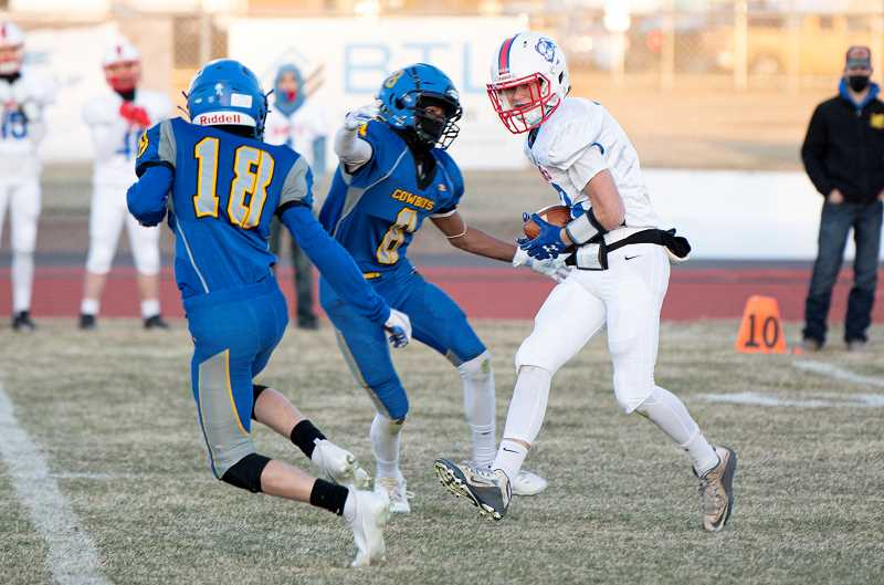 LON AUSTIN  - Ethan Graeme hauls in a pass from quarterback Dru Boyle during the Buffs' 28-0 loss to Crook County March 26. The play went for 61 yards.