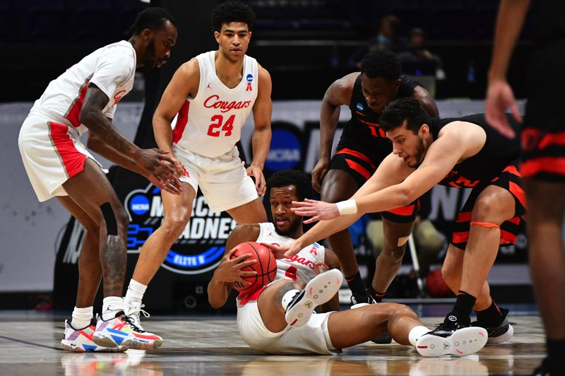 COURTESY PHOTO: NCAA PHOTOS - Houston's Justin Gorham grabs a loose ball as Oregon Stat's Roman Silva (12) and Warith Alatishe (10) scramble after it during a NCAA Men's Basketball regional final game played March 29 at Indianapolis, Indiana. Houston won 67-61 to advance to the Final Four.