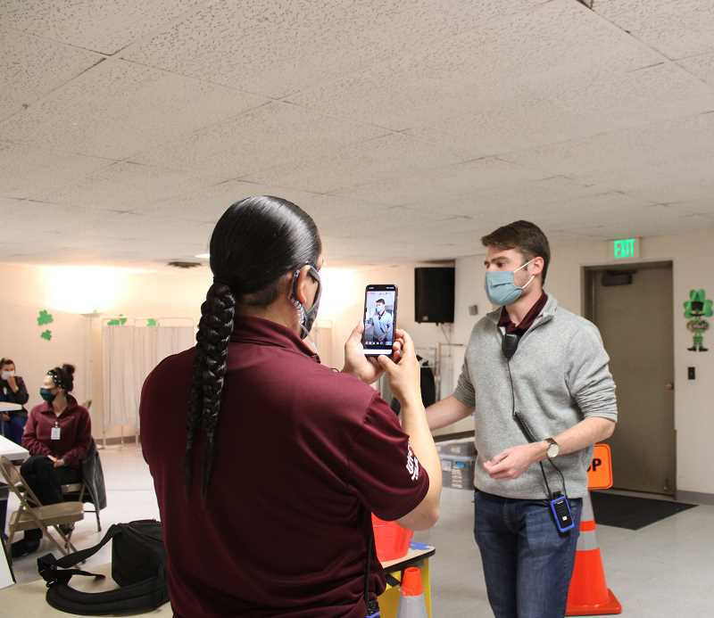 PAT KRUIS/MADRAS PIONEER - Public Health workers Chris Sanders (facing camera) and Johnathan Courtney livestream on Facebook urging newly eligible frontline workers to get their vaccines. The vaccine clinic at First Baptist Church of Madras runs until 4 p.m. Wednesday, March 31.