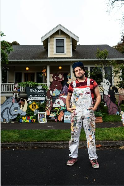 COURTESY PHOTO: MIKE BENNETT - Mike Bennett stands in front of his house and yard in Northeast Portland, site of his fun wooden cartoon cutouts.