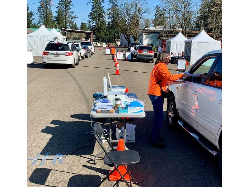 COURTESY PHOTO: KIMBERLY JACOBSEN/OSU EXTENSION - Jan Williams, with the OSU Extension Service in Clackamas County, collects paperwork from participants before they receive their shot at the drive-thru COVID-19 vaccination clinic.