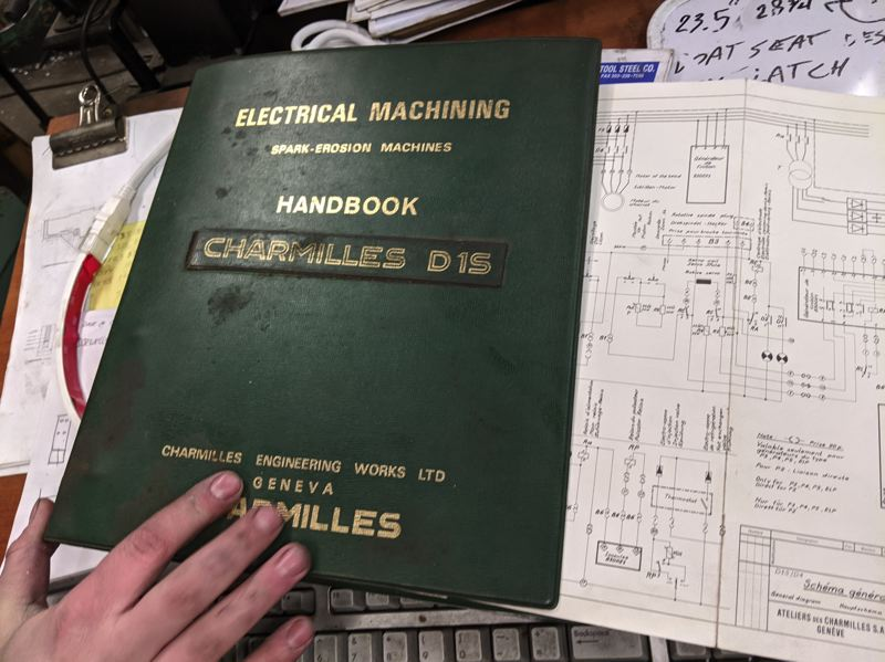 PAMPLIN MEDIA GROUP: JOSEPH GALLIVAN  - Logan Richter showing off the manual for the EDM machine. He stripped the EDM machine and got it working again, using this ring binder full of circuit diagrams. The Electronic Discharge Machining uses a graphite electrode to burn out a hole in metal by arcing.