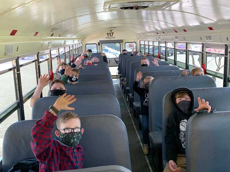 COURTESY PHOTO: OCSD - Oregon City elementary students are required to wear masks while waiting for and riding school buses.