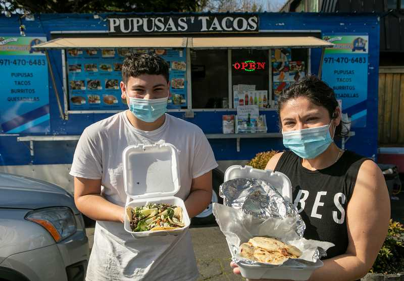 PMG PHOTO: JAIME VALDEZ - Kevin and Cindy Lopez display some of their food fare from their Tacos y Las Pupusas Locas food cart in downtown Tigard.