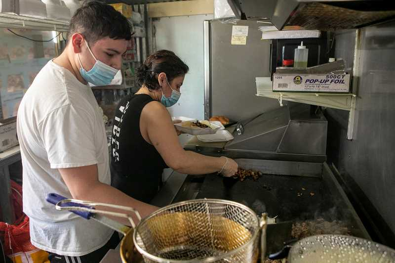 PMG PHOTO: JAIME VALDEZ - Kevin Lopez, left, helps his mother Cindy cook in their downtown Tigard food cart.