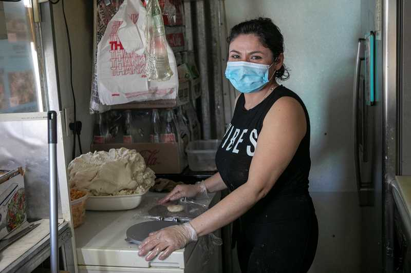 PMG PHOTO: JAIME VALDEZ - Cindy Lopez prepares to cook at Tacos y Las Pupusas in downtown Tigard. The food cart is located on Electric Street, the narrow roadway between Kiss Car Wash and Sherries Jewelry Box.