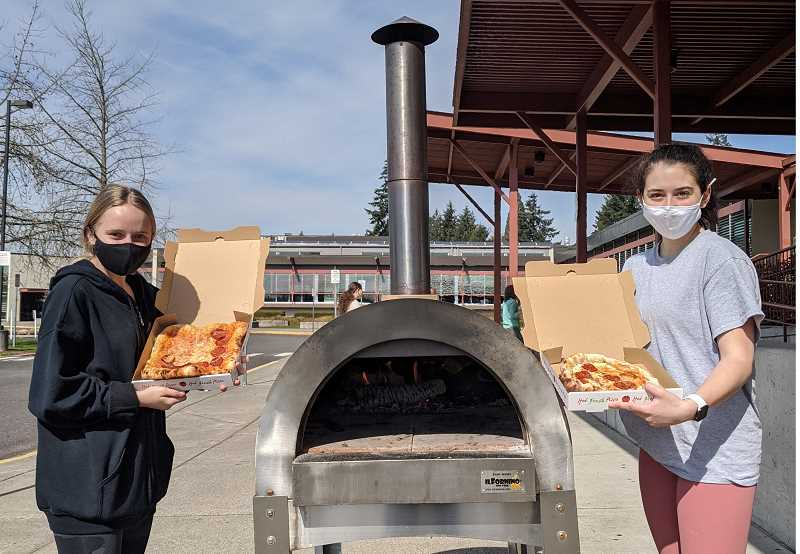 COURTESY PHOTO - Gladstone High School seniors Marissa Gould (left) and Olivia Tipton share the pizzas they made using a wood-fired oven, which was an assignment for their social studies class.