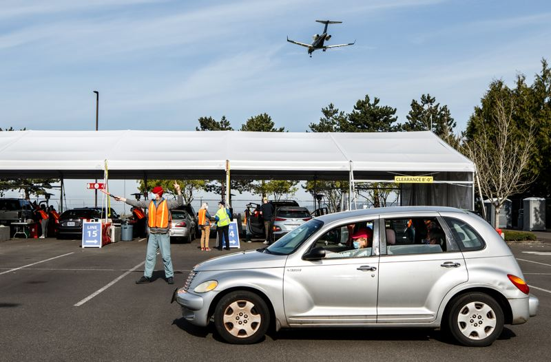 PMG PHOTO: JONATHAN HOUSE - Volunteers at the OHSU Airport Vaccination Site help maneuver cars into the vaccination tent.