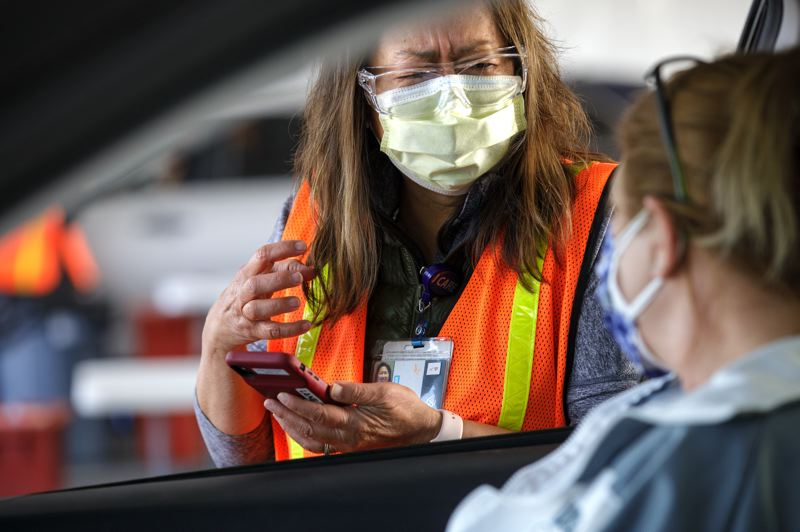 PMG PHOTO: JONATHAN HOUSE - OHSU nurse Jan Haxby chats with a patient before delivering the Pfizer COVID-19 vaccine at the OHSU Airport Vaccination Site.