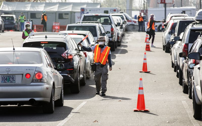 PMG PHOTO: JONATHAN HOUSE - Volunteers at the OHSU Airport Vaccination Site help maneuver cars into the post-shot waiting area.