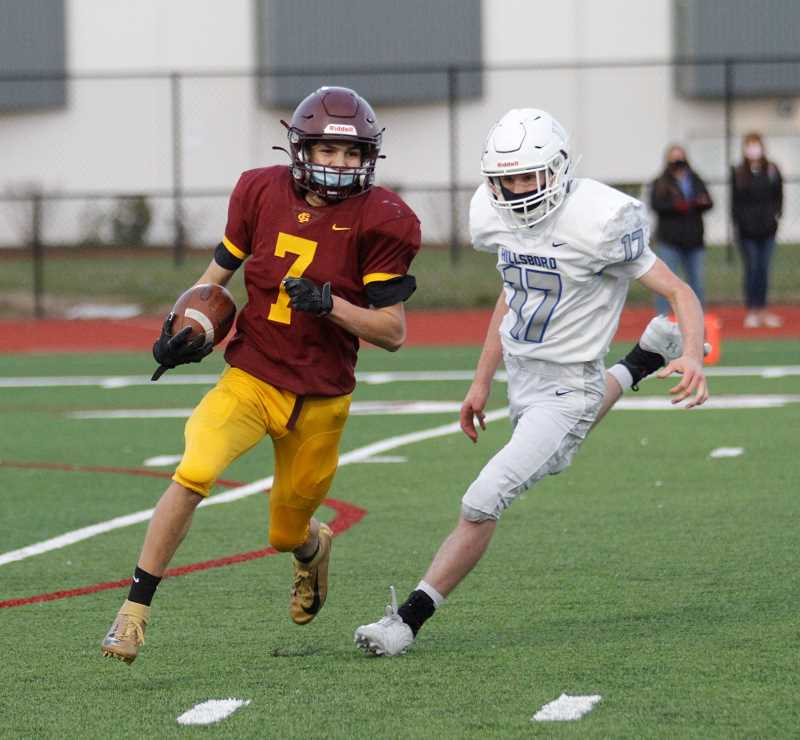 PMG PHOTO: WADE EVANSON - Forest Grove's Kyle Ulloa runs around end while Hillsboro's Jackson Godsey gives chase during the Vikings' game against the Spartans Friday, April 2, at Forest Grove High School.
