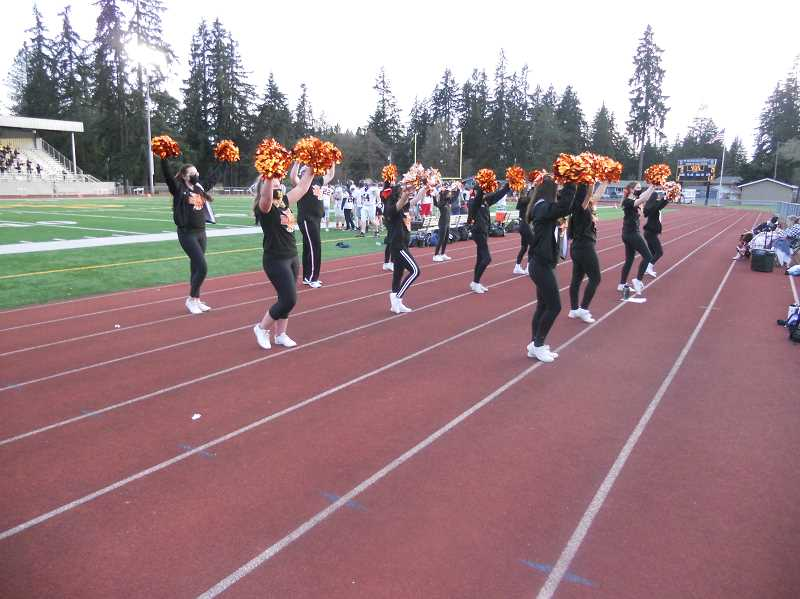 PMG PHOTO: SCOTT KEITH - Scappoose cheerleaders fire-up the visiting Indians crowd during the annual rivalry game between Scappoose and St. Helens high schools Friday night, April 2, at St. Helens High School.