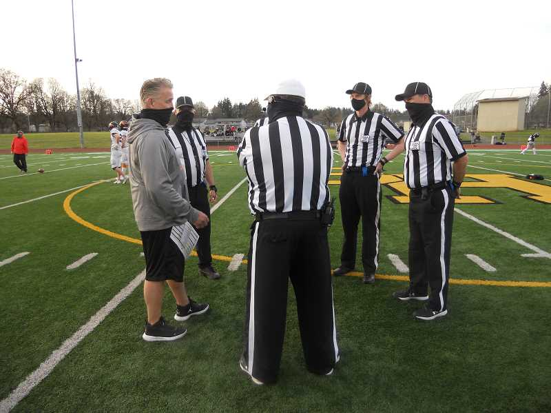 PMG PHOTO: SCOTT KEITH - Scappoose head coach Sean McNabb meets with officials prior to kickoff of the annual rivalry game between Scappoose and St. Helens high schools Friday night, April 2, at St. Helens High School.