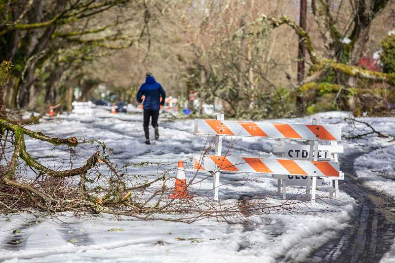 PMG PHOTO: JONATHAN HOUSE - A runner jogs past a road closure sign near the Eastmoreland Golf Course in February. The snow storm in February caused downed trees and power lines, leaving many households without power for days in Portland. Emergency preparedness experts say the snow storm, last year's wildfires and the prospect of an earthquake should remind the region to prepare for the next emergency.