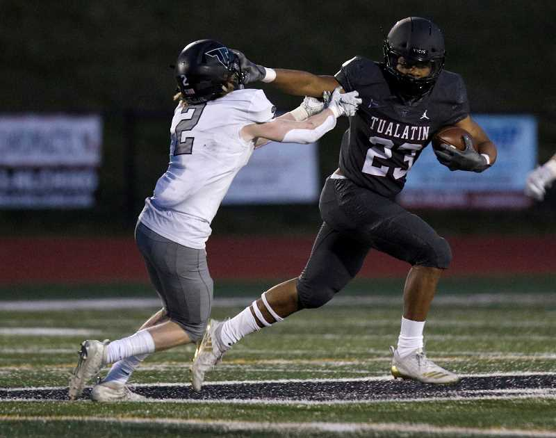 PMG PHOTO: JONATHAN HOUSE - Tualatin's Malik Ross fights off Tigard tacker Hewitt Sullivan during the Timberwolves' game against the Tigers Friday night, April 2, at Tualatin High School.