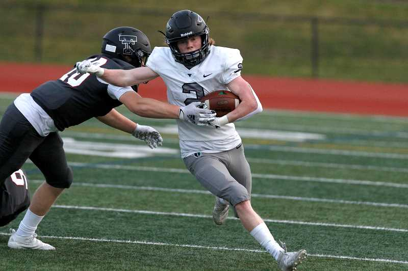 PMG PHOTO: JONATHAN HOUSE - Tigard's Hewitt Sullivan fights off a Tualatin tackler during the Tigers' game against the Timberwolves Friday night, April 2, at Tualatin High School.