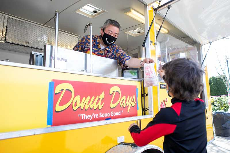 PMG PHOTO: JAIME VALDEZ - Donut Days owner Richard Yep serves mini donuts to the many families who attended the Hop for Spring event.
