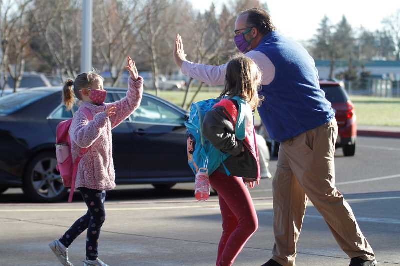 PMG PHOTO: WADE EVANSON - Joseph Gale Principal Troy Fisher greets students with an 'air high five' upon their return to in-person learning Monday morning, April 5, at Joseph Gale Elementary on 18th Avenue.