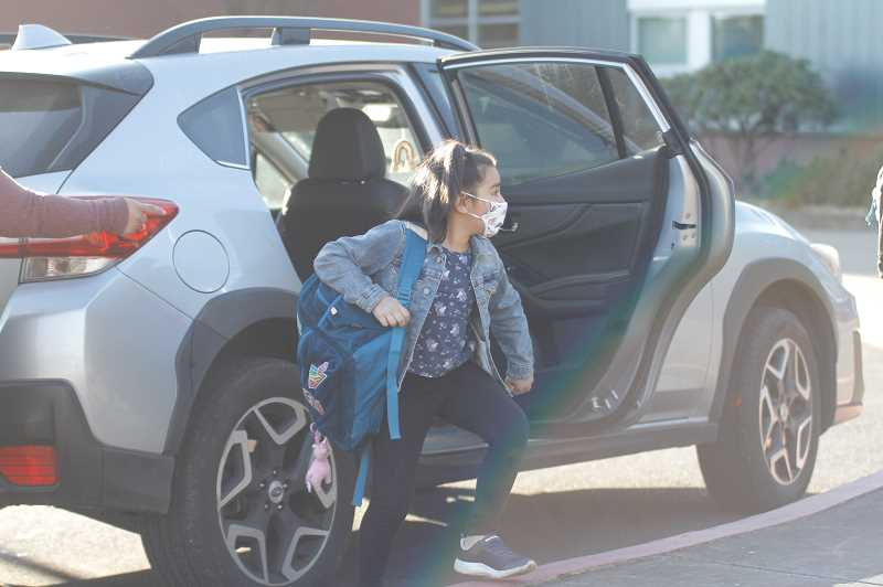 PMG PHOTO: WADE EVANSON - Students piled out of arriving cars at Joseph Gale Elementary School Monday morning, April 5, as in-person learning resumed for Forest Grove area Pre-K through sixth-graders.