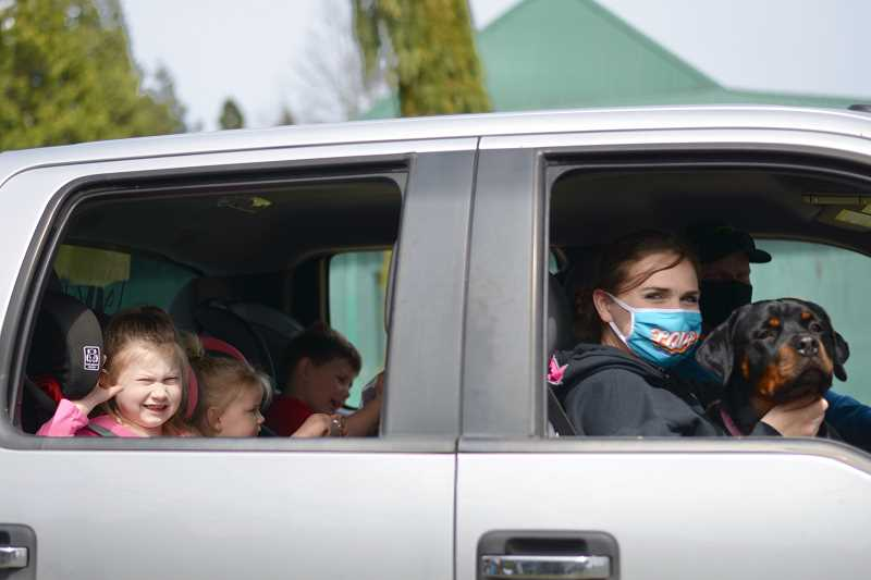 PMG PHOTO: ANNA DEL SAVIO - A family drives through the Columbia County Fairgrounds after picking up goodie bags at the 2021 mEGGa egg hunt.