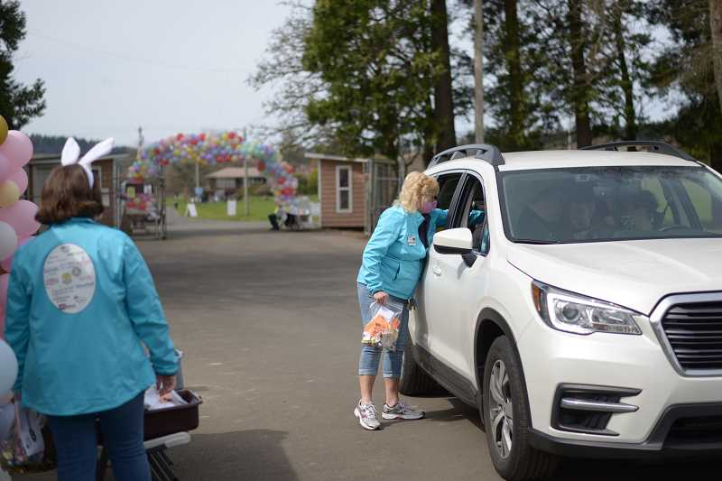 PMG PHOTO: ANNA DEL SAVIO - A volunteer hands goodie bags for kids and adults in a car toward the end of the event.