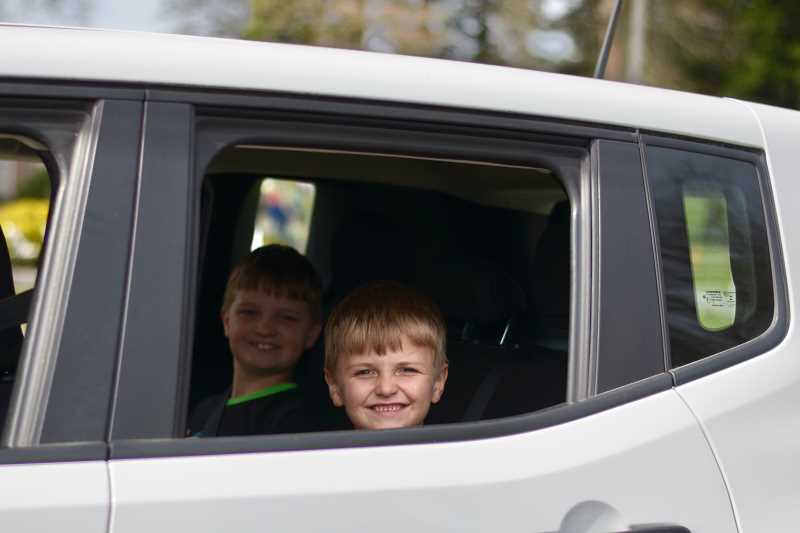 PMG PHOTO: ANNA DEL SAVIO - Kids smile from the backseat after picking up their goodie bags.