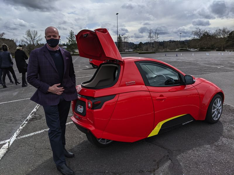 PMG PHOTO: JOSEPH GALLIVAN - ElectraMeccanica CEO Paul Rivera demonstrates the standard cargo hatch at the rear of the Solo EV. It can be replaced by a larger box that Rivera said makes it a practical and economical delivery vehicle.