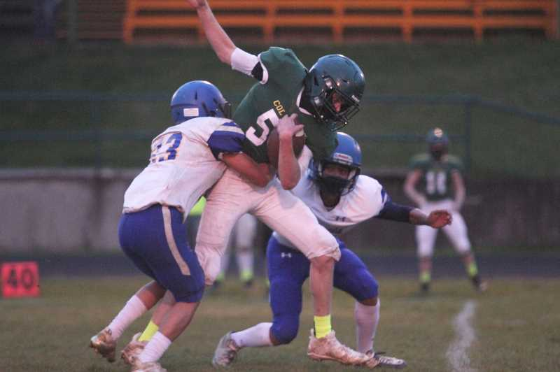 PMG PHOTO: PHIL HAWKINS - Colton sophomore Lance Gunter fights through a pair of would-be tacklers to pick up a first down against the Cougars in the final game of the season for both teams.
