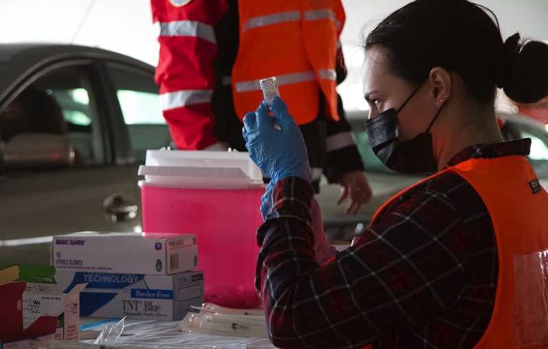 PMG PHOTO: SAM STITES - Volunteers prepare the COVID-19 vaccine to be adminstered at a drive-thru clinic set up at the Clackamas Town Center on March 26.