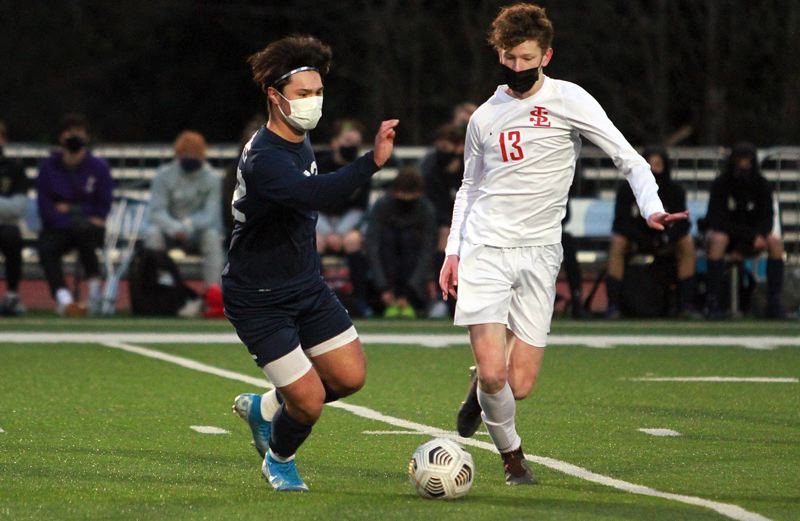 PMG PHOTO: MILES VANCE - Lake Oswego's Eric Seaman (left) and La Salle's Jeffrey Richter battle for control of the ball during the Falcons' 3-2 win over the Lakers at Lake Oswego High School on Wednesday, April 7.