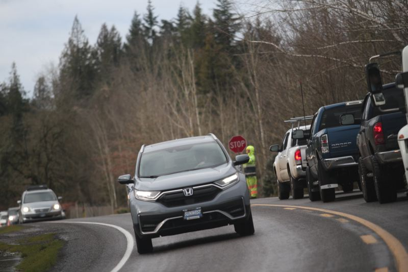 PMG PHOTO: PHIL HAWKINS - Flaggers control highway traffic as crews clear debris from the road in the aftermath of a heavy ice storm that pelted much of the Willamette Valley in February 2021.