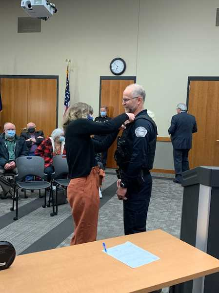 COURTESY PHOTO - Karen Tro pins the badge on new Canby Police Chief Jorge Tro.
