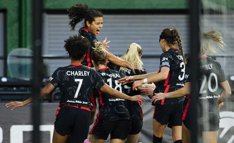 COURTESY PHOTO: CRAIG MITCHELLDYER/PORTLAND THORNS FC - Teammates rush to celebrate with Rockey Rodriguez after the Thorns midfielder scored the firt goal of 2021 in Portland's 2021 National Women's Soccer Club Challenge Cup opener at Providence Park.