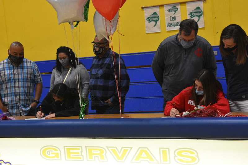 COURTESY PHOTO: JEREMY MCDONALD/JMCDONALDMEDIA - Araceli Vasquez (left) and Katie Hansen sit in the Gervais High School gymnasium to sign their letters of intent to compete in collegiate basketball for the 2021-22 season. Vasquez will join the Chemeketa Storm while Hanson will play for the Lower Columbia Red Devils.