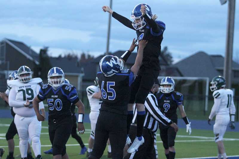 PMG PHOTO: PHIL HAWKINS - Woodburn's Jordan Blem leaps into the arms of Santiago Roque Manzo following a touchdown run in the second quarter to give the Bulldogs a 15-8 edge heading into halftime of Fridays 37-28 win over North Marion.