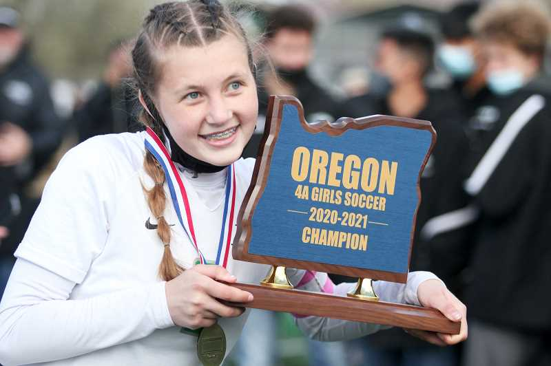 PMG PHOTO: PHIL HAWKINS - North Marion senior Hailey Welch displays the 4A girls soccer 2020-21 championship trophy. While it remains to be seen if the OSAA counts the championship game as an official title for the record book, the Huskies view the tournament championship win as the first state title in program history.