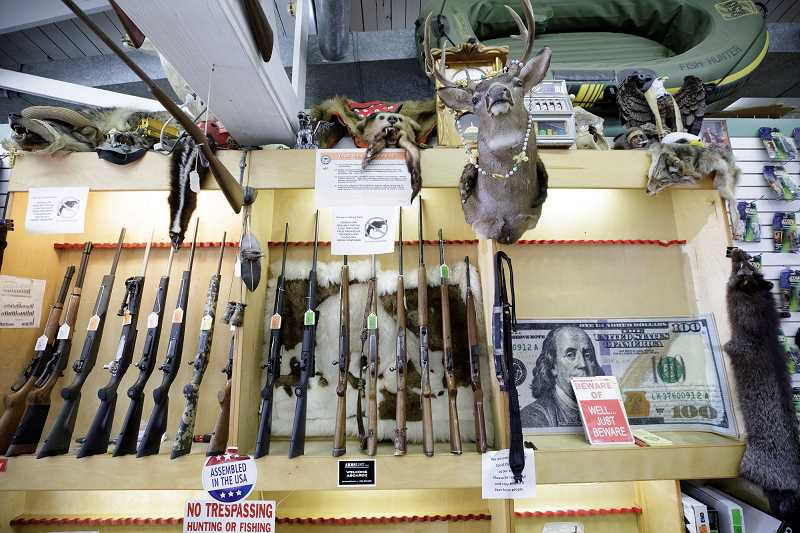PMG PHOTO: JONATHAN HOUSE - Firearms for sale line the wall at a pawn shop.