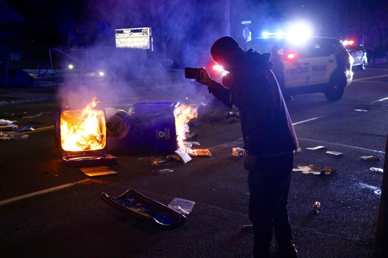 PMG PHOTO: ZANE SPARLING - Recycling cans were lit on fire and strewn across East Burnside Street after Portland Police declared a riot during a protest on April 12.